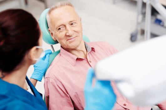An older man sat in the dentist chair